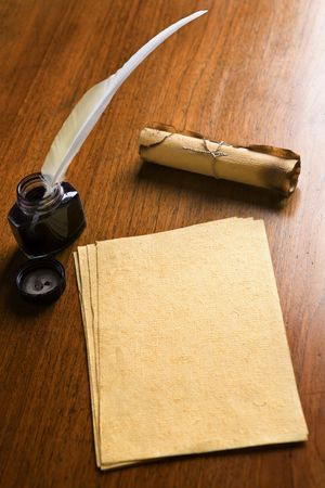Old paper, quill pen and scroll on wooden table photo