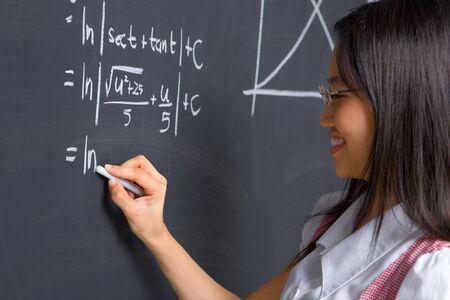 scholars: De trabajo femenino de los estudios sobre matem�ticas problema en la pizarra Foto de archivo