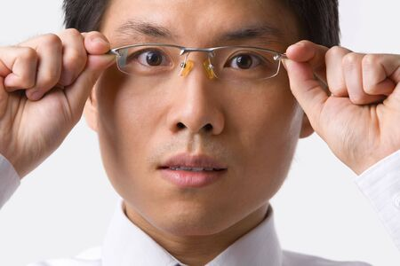 A young Asian businessman gazing at camera while holding glasses to camera Stock Photo - 5128058