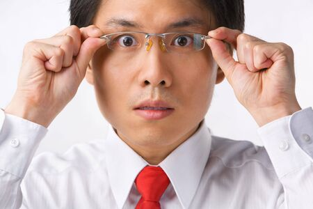 A young Asian businessman gazing at camera while holding glasses to camera with surprised expression Stock Photo - 5128064