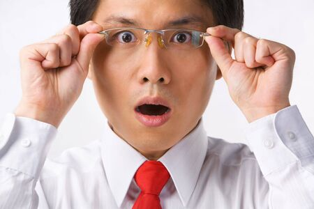 unbelievable: A young Asian businessman gazing at camera while holding glasses to camera with surprised expression