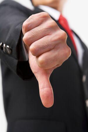 pollice in gi: Un uomo d'affari che mostra il pollice verso il basso per respingere