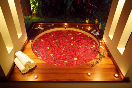 bathtub: A private spa bathtub at night condition, the tub full of rose petal