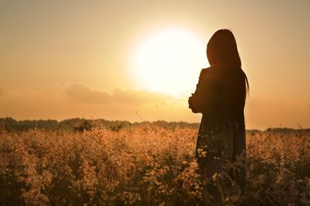 early summer: Woman silhouette waiting for summer sun on meadow