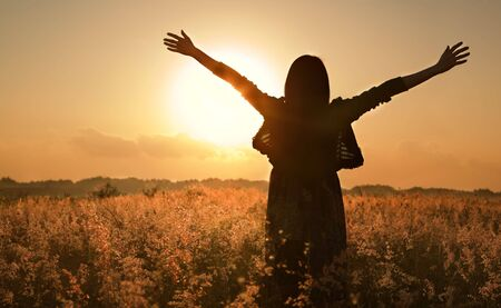 breathe: Woman silhouette waiting for summer sun on meadow