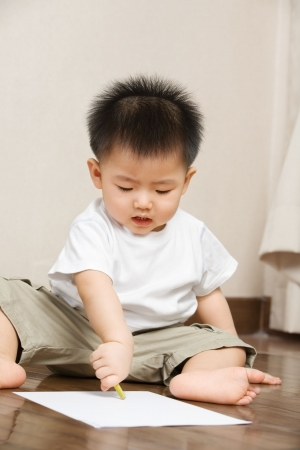 Asian toddler busy drawing on a paper photo