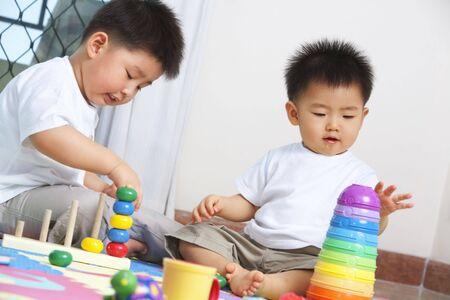 hermanos jugando: Hermanos que juegan juntos y compartiendo la juguetes en el hogar Foto de archivo