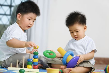 Brothers playing together and sahring toys at home photo