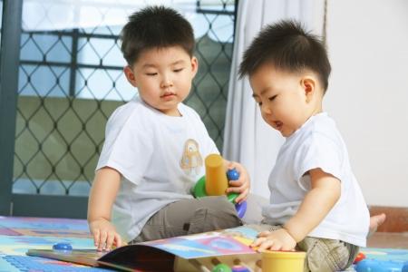 bambini cinesi: Fratelli che giocano insieme e giocattoli sahring a casa