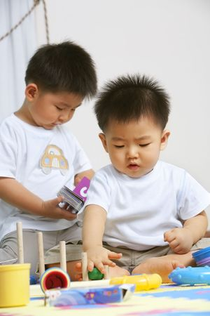 babies playing: Brothers playing together and sahring toys at home