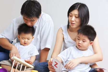 Young Asian family spending time together, teaching and playing together with their sons photo