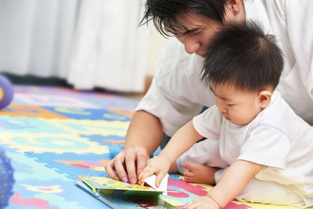 Father spending time with his little boy and tutoring him to learn reading photo