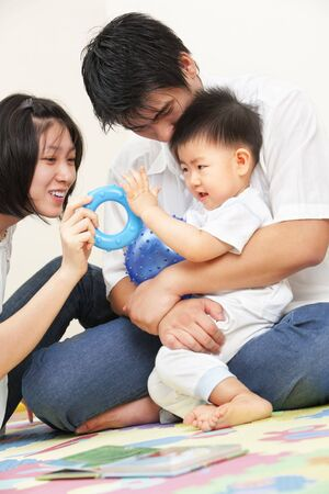 Asian young family spending time together, playing with their little son photo