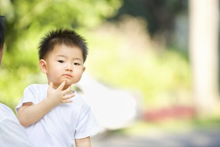 Asian toddler thinking in outdoor area with enough copy space photo