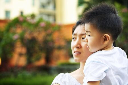 Mother and son waiting father to come home in apartment's garden area in the afternoon photo