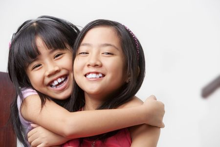 asian home: two little girl showing their affection posing to camera