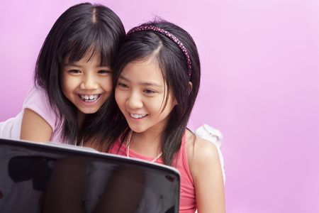 Little girls playing laptop in the bedroom with pink copy space Stock Photo - 5386669