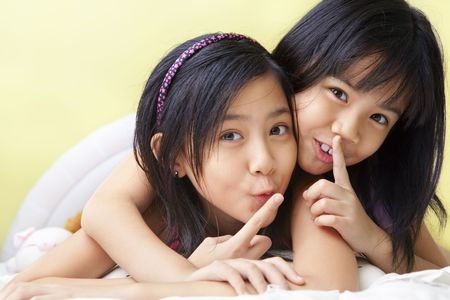 shh: young little girls sshhh to camera not to telling their secret