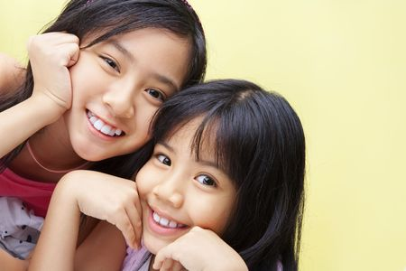 Two little girls posing to camera together happily photo
