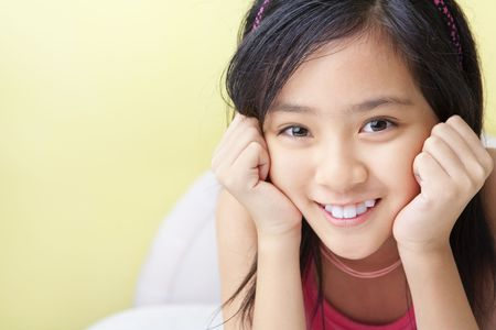 cute kid: A cute Asian little girls posing on her bed Stock Photo