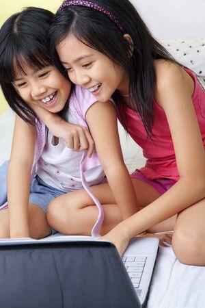 laptop asian: Las ni�as utilizando equipo port�til en su habitaci�n Foto de archivo