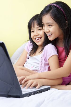 Little girls using laptop in their bedroom Stock Photo - 5386667