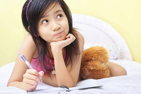 pen writing: A little girl writing her diary in her bedroom