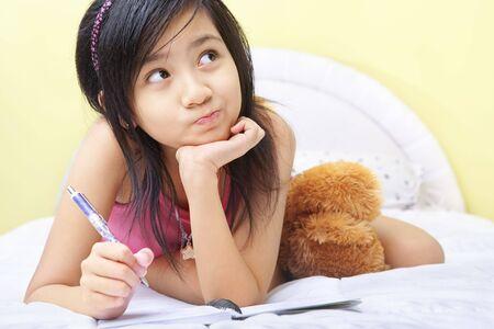 ni�os escribiendo: Una ni�a a escribir su diario en su dormitorio Foto de archivo