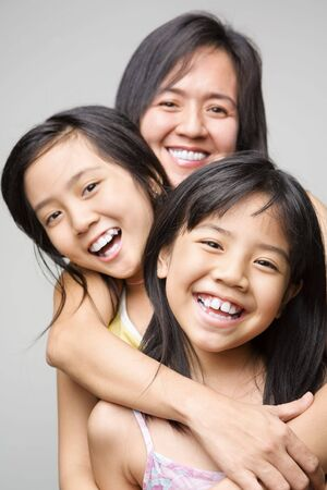 three generations of women: Mother hugging her daughters and posing to camera