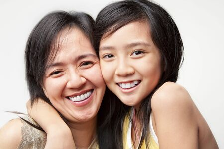 asian mother and daughter: little girl hugging her mother and posing to camera