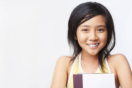 Little girl holding book, posing to camera