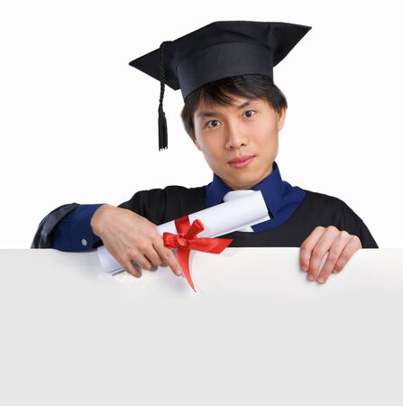 scholar: Graduated scholar pointing to blank white board Stock Photo
