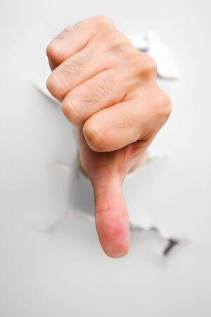 pollice in gi: Pollice verso il basso � venuto dalla parete crack - uno della serie rivoluzionarie. PS: si concentra sul pollice Archivio Fotografico