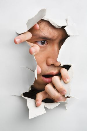 Man looks displeasure from cracked wall - one of the breakthrough series Stock Photo
