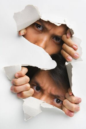 hole in wall: Two people peeking from hole in wall showing their eyes only Stock Photo