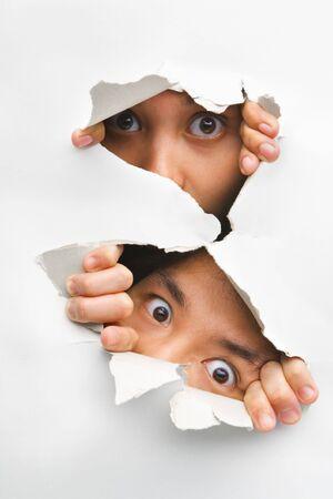 descubrir: Dos personas asom�ndose del agujero en la pared mostrando sus ojos s�lo Foto de archivo