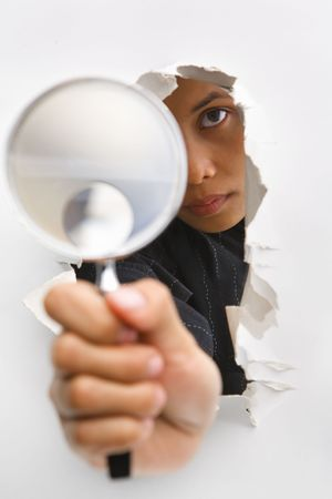 ps: Detective holding magnifying glass from cracked wall means breakthrough in investigation - one of the breakthrough series. PS : focus on the womans eye