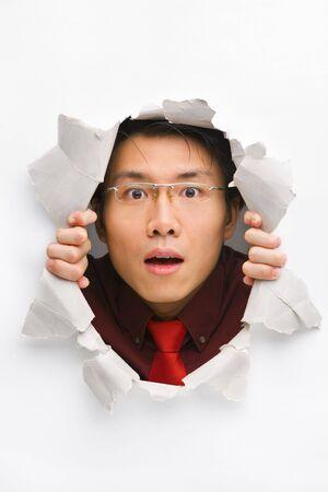 cara sorprendida: Hombre mirando sorprendentemente del agujero en la pared con el espacio de la copia en posici�n horizontal