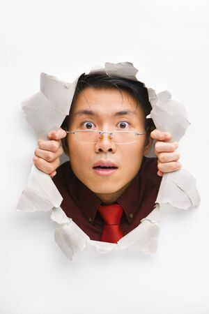 Man with funny expression gazing from hole in wall Stock Photo - 5468881