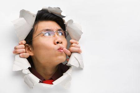 Hombre reflexivo del agujero en la pared buscando seriamente su lado izquierdo en blanco