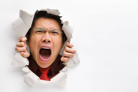 horizontal position: Man screaming from the hole in wall with copy space in horizontal position Stock Photo