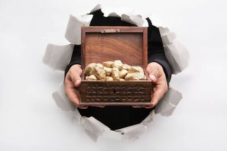 Hand breakthrough wall holding golden nuggets in treasure chest means breakthrough in finance or similar things - one of the breakthrough series photo