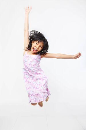 Joyful kid jumping high over white background. PS : motion blur photo