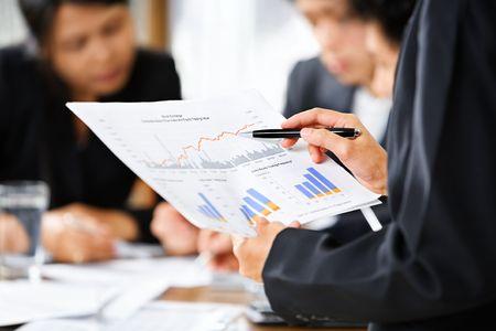 Geschäftsfrau Prüfung Graphen mit anderen Werktätigen auf den Hintergrund