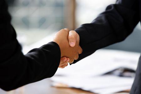 close up image of handshake between two businesswomen. Different skin tones