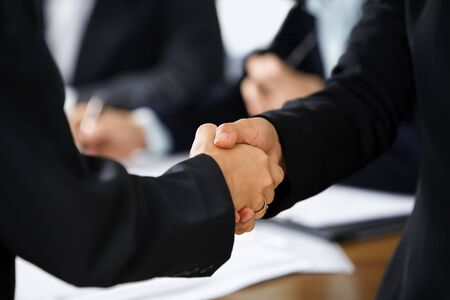 Handshake between two businesswoman with other business people on background. Different skin tones photo