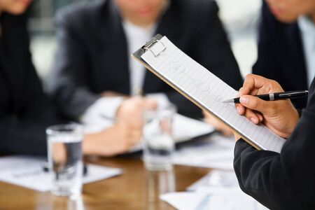 cohesive: businesswomans hand writing with other business people in background