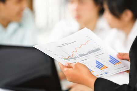 cohesive: Businesswoman examining graphs with other working people on background