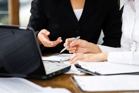 cohesive: Discussion between two women in office, with laptop and documents on table