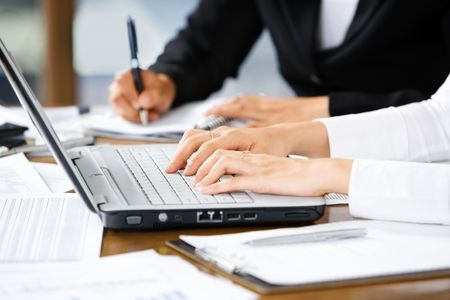cohesive: Woking people in office, with one typing the laptop and the other writing on paper Stock Photo
